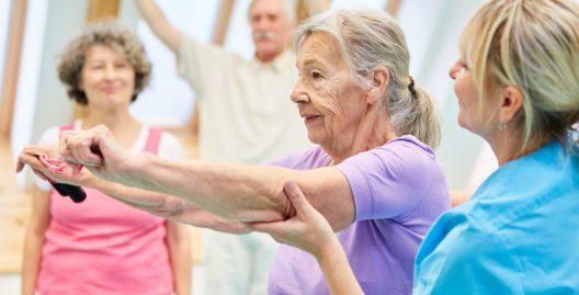 Senior Frau in der Physiotherapie macht Übung mit Elastikband mit Hilfe von Trainerin