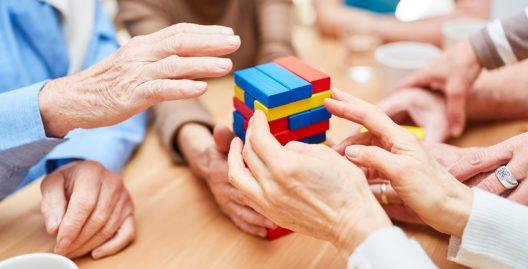 Gruppe Senioren mit Demenz baut aus bunten Bausteinen einen Turm im Pflegeheim
